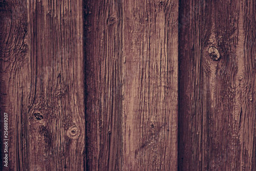 Brown wooden retro table. Red wooden wall background in rustic style. Old brown wall wood vintage floor. Wooden fence maroon painted. Wood brown boards texture.