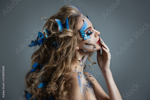 Girl with butterflies in her hair and gorgeous eye makeup Wallpaper Mural