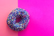 Leinwanddruck Bild - sweet Donut with icing and colored sprinkles, on a pink background, top view