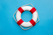 Red And White Striped Lifebelt On Slightly Textured Blue Paper Background