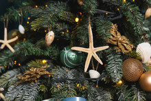 Christmas Decoration In Gold And Blue Colors. New Year Decoration In Nautical Style. Seashells, Seahorse And Stars In The Design Of The Christmas Tree On A Blue Background. Starfish, Ribbons And Balls