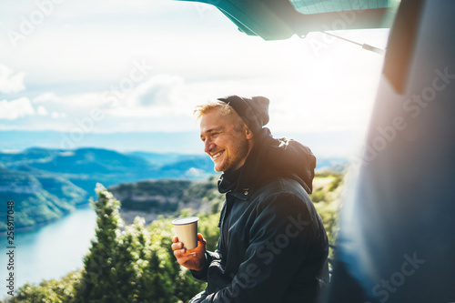 Canvastavla  hipster tourist hold in hands mug of hot drink, lonely guy smile enjoy sun flare