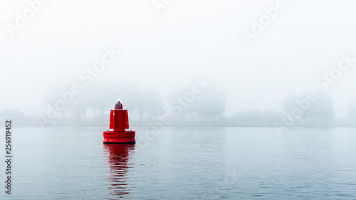 Photo Red buoy in a river in the mist