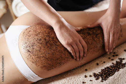 Fotografie, Obraz Close up of woman getting buttocks and legs massage with coffee scrub at spa