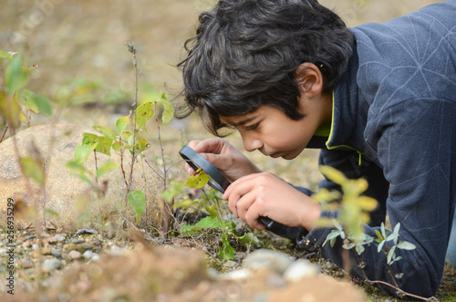 Fotografering a boy in nature sitting on the ground looking at a magnifying glass plants