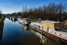The Canal Boat And Repair Yard In Sawbridgeworth With Derelict Canal Boats Awaiting Repairs On A Sunny Day In Winter.