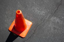 An Orange Cone On The Side Of The Image, On The Pavement