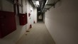 Long white corridor with fire extinguishers in the basement of house