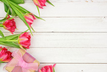 Side Border Of Pink Flowers With Gift Box Against A Rustic White Wood Background