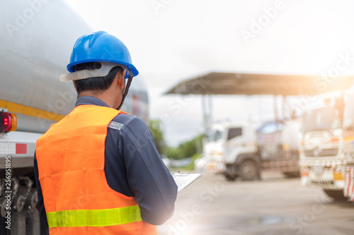 Fototapety, obrazy: Preforming a pre-trip inspection on a truck,Concept preventive maintenance truck checklist,Truck driver holding clipboard with checking of truck,spot focus.