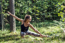 Kung Fu Girl Training In The Forest. A Cute Female Practicing Martial Arts In The Park.