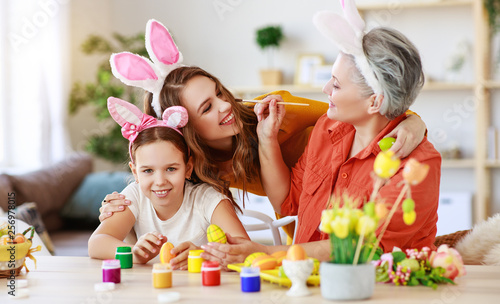 happy Easter! family grandmother, mother and child paint eggs and prepare for holiday Canvas Print