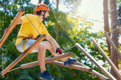 Fotografie, Obraz  Young male man adult wears protective helmet with action camera having fun in extreme rope park, amusement park