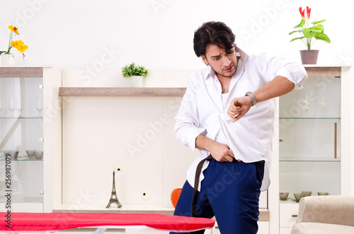 Cuadros en Lienzo Young man ironing in the bedroom