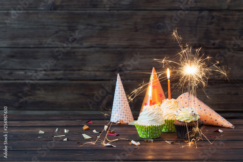 Fotografía birthday cupcakes with candles on old dark  wooden background