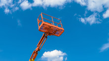 Cherry Picker On Blue Sky Background. Boom With Lift Bucket Of Heavy Machinery. Orange Platform Of The Telescopic Construction Lift In Summer.