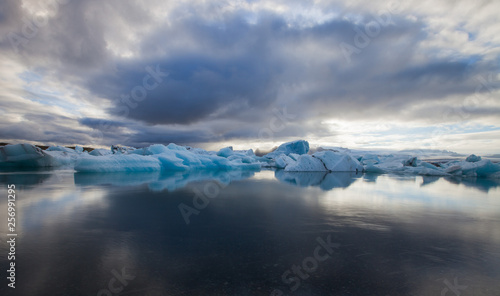 Poster Glaciers Dramatic a sunset with mirror water with blue iceberg pieces in Jokulsarlon lagoon, Iceland.