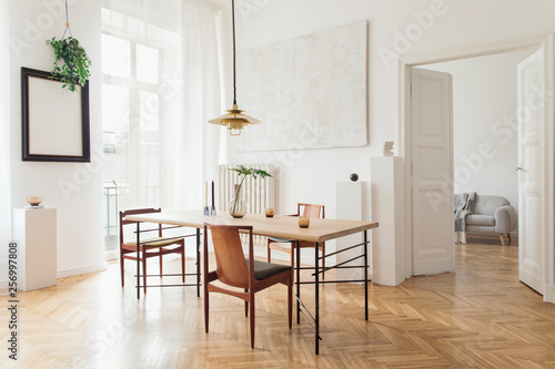 Eclectic and elegant dining room interior with design sharing table, chairs, gold pedant lamp, abstract paintings and stylish accessories Tablou Canvas