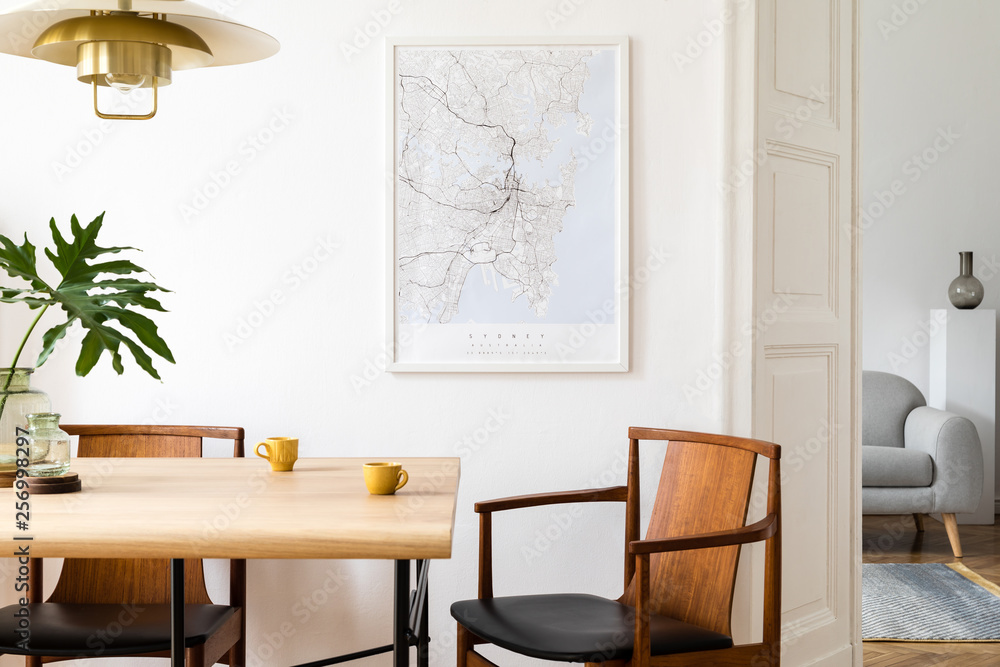 Fototapety, obrazy: Stylish and eclectic dining room interior with mock up poster map, sharing table design chairs, gold pedant lamp and elegant sofa in second space. White walls, wooden parquet. Tropical leafs in vase.