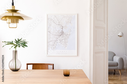 Fotografie, Tablou  Stylish and eclectic dining room interior with mock up poster map, sharing table design chairs, gold pedant lamp and elegant sofa in second space