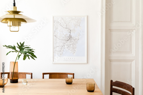 Valokuva  Stylish and modern dining room interior with mock up poster map, sharing table design chairs, gold pedant lamp and cups of coffee