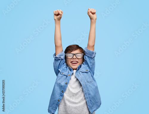 Fotografie, Tablou  Happy kid in glasses holding hands up