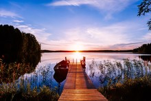 Wooden Pier With Fishing Boat At Sunset On A Lake In Finland