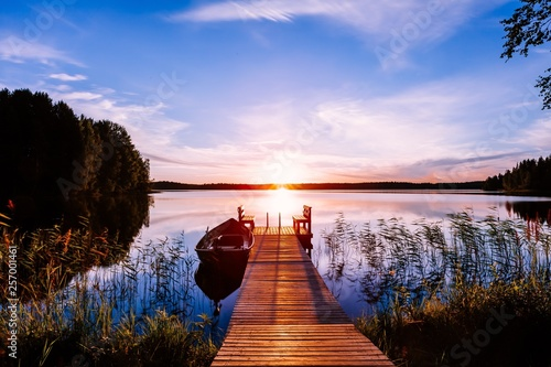 Garden Poster Black Wooden pier with fishing boat at sunset on a lake in Finland
