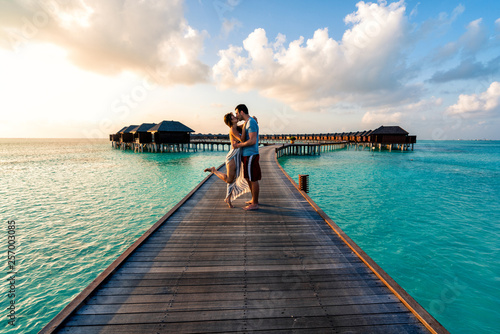 A couple enjoying a sunrise in the Maldives. Obraz na płótnie