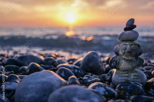 hareubang pebble reflection at sunset over the sea - zen and relaxation