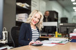 blonde 30s woman working at office and smiling