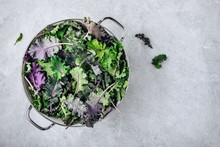 Green Baby Kale Leaves In White Colander On Gray Stone Background. Ingredient For Healthy  Smoothie, Salads Or Pesto Sauce