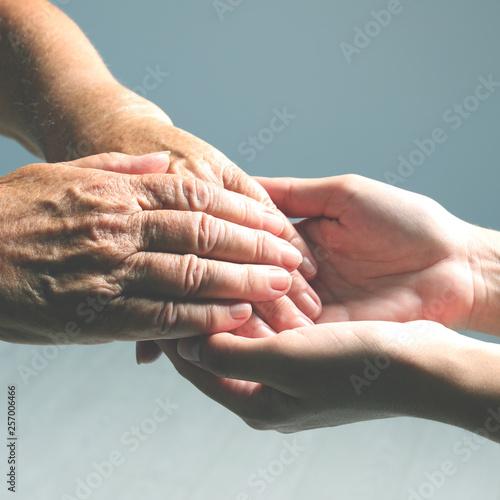 Volunteer holding hand of senior woman against light background, closeup Wallpaper Mural