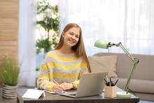 Pretty Teenage Girl Doing Homework At Table In Room