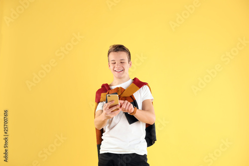 Handsome teenage boy using mobile phone on color background