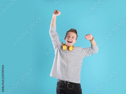 Fotografiet  Portrait of emotional teenage boy with headphones on color background