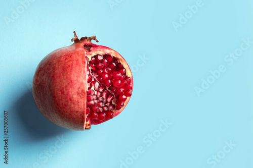 Ripe pomegranate on color background, top view with space for text - 257008607