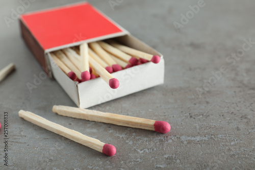 Open box and scattered matches on grey background, space for text Canvas Print