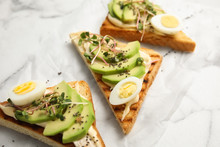 Tasty Toasts With Avocado, Quail Eggs And Chia Seeds On Marble Background