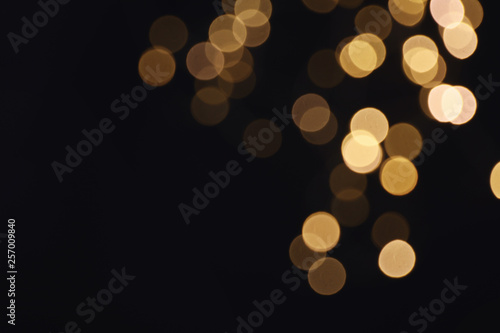 Obraz Beautiful golden lights on dark background. Bokeh effect - fototapety do salonu