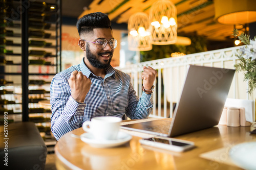 Fotografía  Overjoyed hipster indian guy cheers for team watching match on laptop computer d
