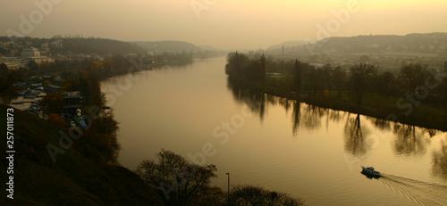 Fotografie, Obraz  Vltava River at sunset with reflection of trees in Prague