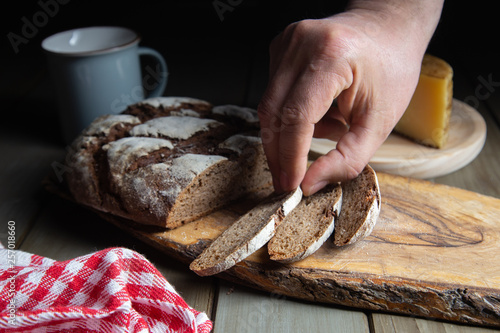 Deurstickers Bakkerij male hand picking up a slice of rye bread on a rustic table with a plaid cloth and a cheese