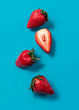Red strawberry floating on blue background. Minimal food idea concept. Bright colors, flat lay