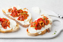 Ricotta And Sun Dried Tomatoes Sandwiches On White Board.