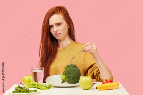 Fotografija Sad red-haired woman in bad temper keeping strict vegetarian diet being tired of restrictions and hates greenery