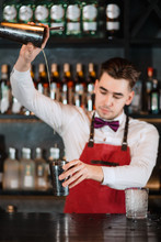 Creative Barman Making Alcoholic Drink, Pouring Fresh Cocktail From Shaker Into Matalic Glass On The Bar Stand