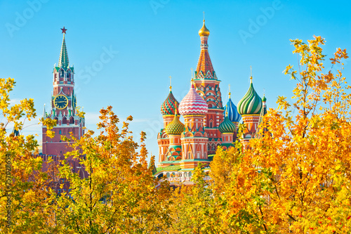 Poster Moscow Spasskaya Tower and Cathedral of Vasily the Blessed (Saint Basil's Cathedral). Red Square. Golden foliage of trees. Sunny autumn day, blue sky. Moscow. Russia
