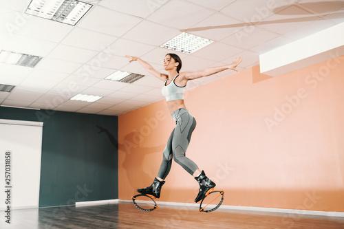 Fotografia  Attractive Caucasian brunette in sportswear and kangoo jumps footwear jumping in gym