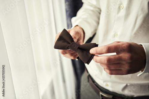Fotografía  businessman putting on  bow tie,man butterfly clothes,groom getting ready in the morning before wedding ceremony